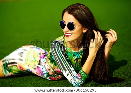 Funny crazy glamor stylish sexy smiling beautiful  young woman model in hipster green dress sitting in the grass in the park - stock photo