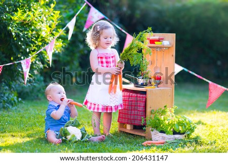 Funny curly little girl and adorable baby boy, cute brother and sister, playing together with a vintage wooden toy kitchen, table ware and fresh healthy vegetables in a sunny summer garden - stock photo
