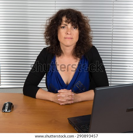 Funny curly woman at her desk at office - stock photo