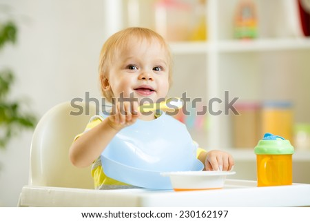 funny cute baby kid boy eating itself with spoon in kitchen - stock photo