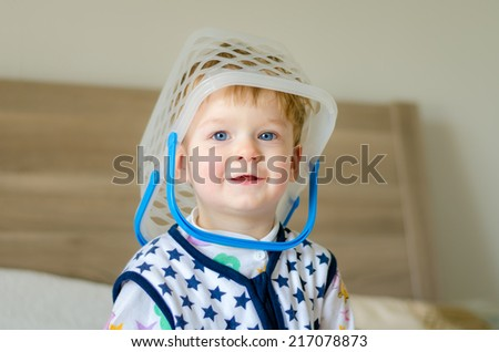 Funny cute baby kid with busket on his head is playing at home - stock photo