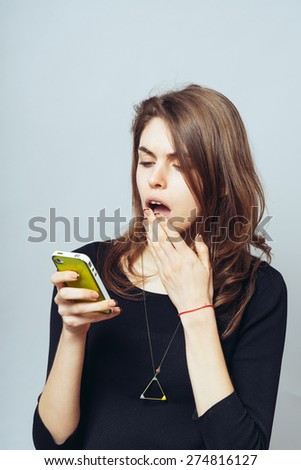 funny cute brunette girl dials sms on mobile phone - stock photo