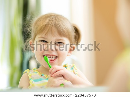 funny cute child girl brushing teeth in bathroom - stock photo