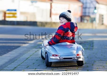 Funny cute child in red jacket driving big vintage old toy car and having fun, outdoors. Kids leisure on cold day in winter, autumn or spring. - stock photo