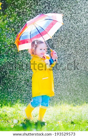 Funny cute curly toddler girl wearing yellow waterproof coat and boots holding colorful umbrella playing in the garden by rain and sun weather on a warm autumn or summer day - stock photo
