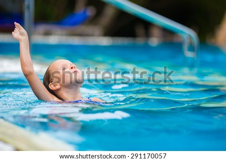 Funny cute girl in outdoor swimming pool - stock photo