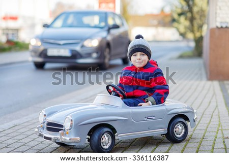 Funny cute kid boy in red bright jacket driving big vintage old toy car and having fun, outdoors. Active leisure for kids on cold day in winter, autumn or spring. - stock photo