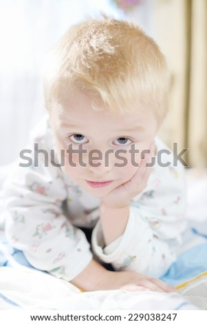 Funny cute little child in pajamas with blonde hair - stock photo