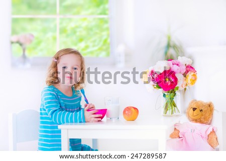 Funny cute little girl in a blue dress eating healthy breakfast - fruit, cereal and milk, feeding her toy bear in a white sunny kitchen - stock photo