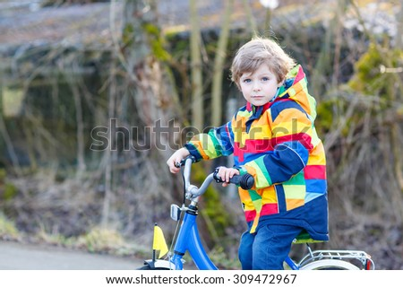 Funny cute  preschool kid boy in colorful raincoat riding his first bike and having fun on warm  day, outdoors. Active leisure with children in winter, sping or autumn. - stock photo