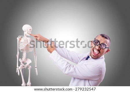 Funny doctor with skeleton isolated on white - stock photo