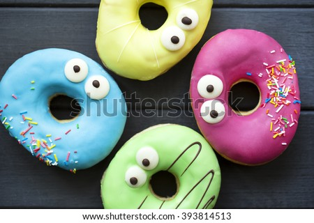 funny donuts on a gray wooden background  - stock photo