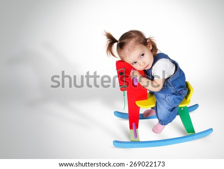 funny dreaming little girl rides toy horse - stock photo