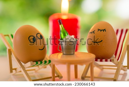 funny eggs on a beach chair relaxing and flaming candle with christmas tree bokeh behind - stock photo