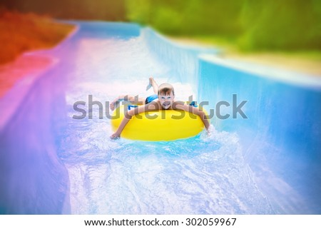 Funny excited child enjoying summer vacation in water park riding on slide with yellow float - stock photo