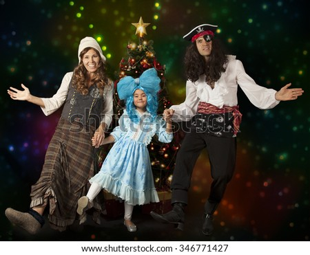 Funny family in carnival costumes dancing in front of Christmas tree
