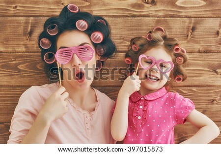 Funny family! Mother and her child daughter girl with a paper accessories. Beauty funny girl holding paper glasses on stick. Beautiful young woman holding paper glasses on stick. - stock photo