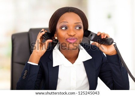 funny female african american office worker talking on landline and mobile phone at same time - stock photo