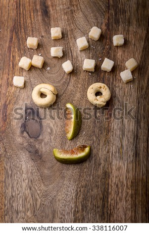 funny food face made with fig, parmesan and taralli on wood - stock photo