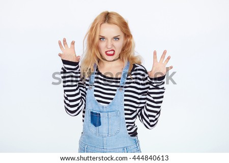 Funny girl acts as bad cat. Blond hair young woman having fun and showing her clutches on white background isolated - stock photo