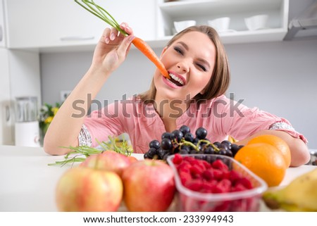 Funny girl biting a carrot, she eating healthy food  - stock photo
