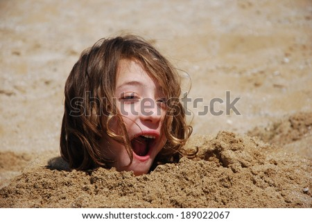 Funny Girl Buried in the Sand at the Beach - stock photo