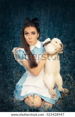 Funny Girl Costumed as Alice in Wonderland with The White Rabbit - Portrait of a surprised girl in a blue costume holding a white bunny  - stock photo