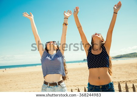 Funny girl friends with arms outstretched greeting the sun on the beach - stock photo