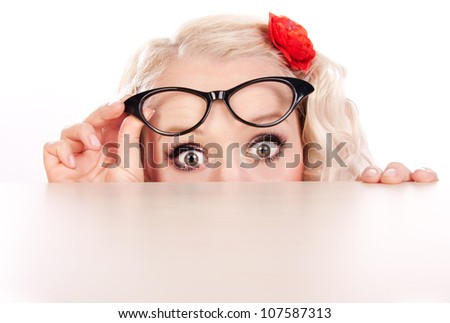 Funny girl hiding behind a table - stock photo