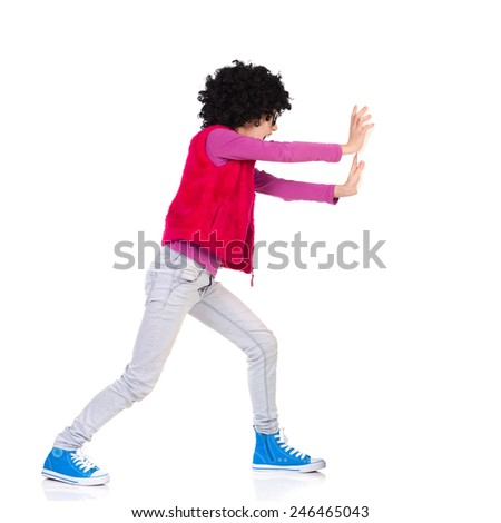 Funny girl in curly wig and black glasses pushing a wall. Full length studio shot isolated on white. - stock photo