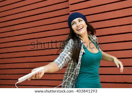 Funny girl listening to the music with earphones from a smart phone over red bricks wall background. - stock photo