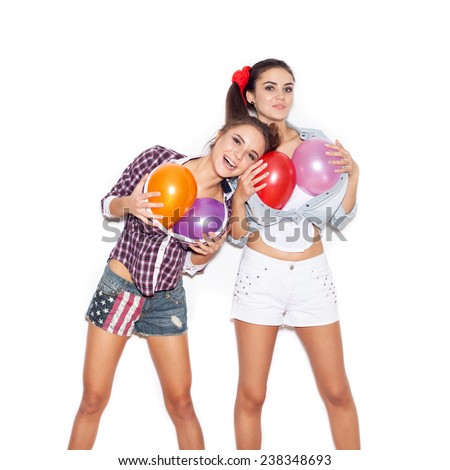 Funny girl put her head on the chest of colored balloons her friend. Women having fun.  White background not isolated - stock photo
