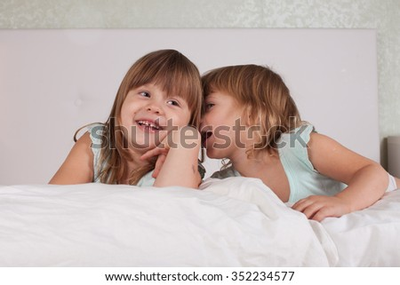 funny girl siblings sisters communication secrets on the bed with pillows, fool around, light background - stock photo