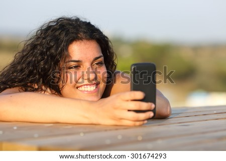 Funny girl watching social media in smart phone relaxing in a park - stock photo