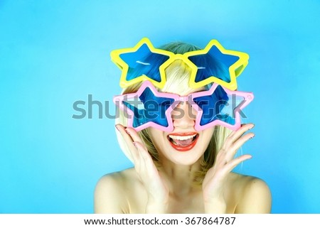 Funny girl wearing star shaped glasses, Playful girl with funny glasses, Happy naughty blonde hair woman with Large glasses. Party time. - stock photo