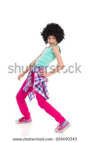 Funny girl with afro hair. Dancing teen girl wearing afro wig. Three quarter length studio shot isolated on white. - stock photo