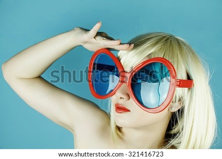 Funny girl with funny glasses, Happy naughty blonde hair woman with giant sunglasses. Woman in crazy clown glasses, Large funny glasses. Looking forward.(Vintage Style Color) - stock photo