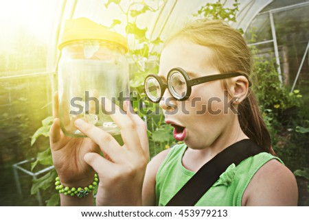 Funny girl with glasses and butterfly in a jar. - stock photo