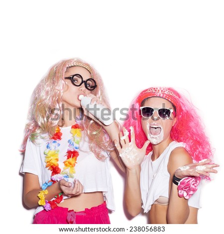 Funny girls in colored wigs and glasses stained with cream on white background not isolated - stock photo