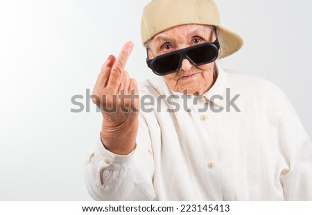 Funny grandma's studio portrait  wearing eyeglasses and baseball cap, who shows her f-finger ,  isolated on white - stock photo