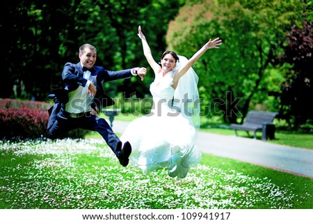 funny groom and bride jumping - stock photo