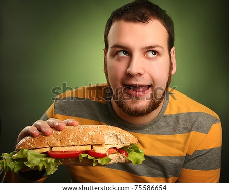 funny guy eating hamburger on green background - stock photo