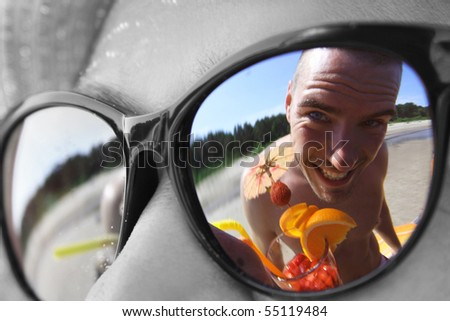 funny guy with cocktail reflecting in sunglasses - stock photo