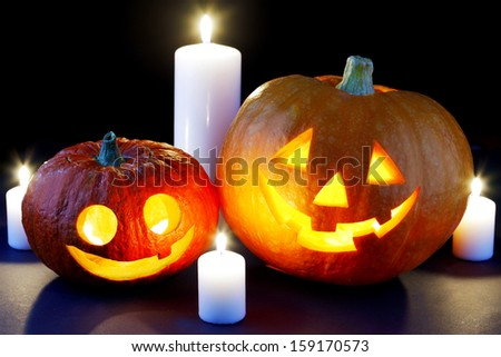 Funny Halloween pumpkins and burning candles - stock photo