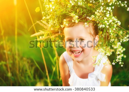 funny happy baby child girl in a wreath on the nature laughing in a meadow in summer - stock photo