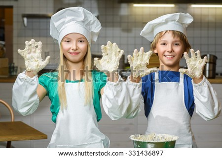 Funny happy chef boy width girl cooking at restaurant kitchen and knead the dough in a bowl - stock photo