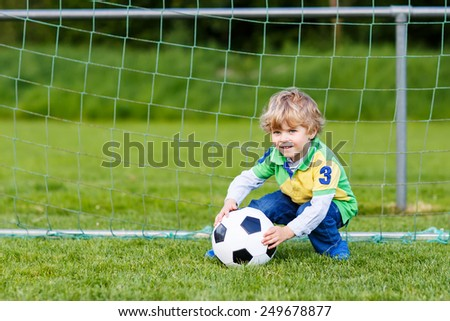 Funny happy little kid boy playing soccer and football and having fun, outdoors on field. Active leisure with children on warm sunny summer day. - stock photo