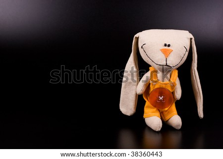 Funny hare toy on black background with copyspace - stock photo