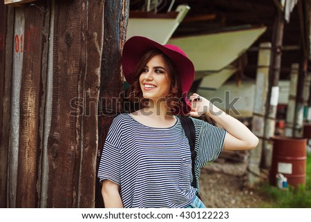 Funny Hipster Girl in old boat garage in island, Lots of boats.Trendy Casual Fashion Outfit in summer,spring. Toned Photo. - stock photo