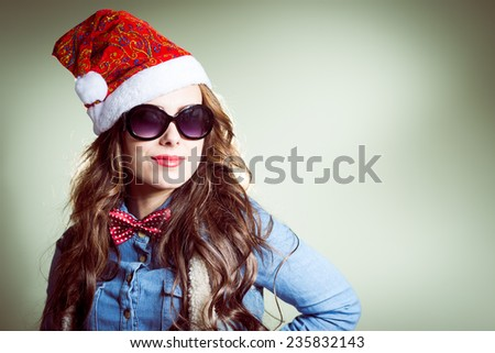 Funny hipster girl in sunglasses wearing xmas santa hat over olive copy space background - stock photo